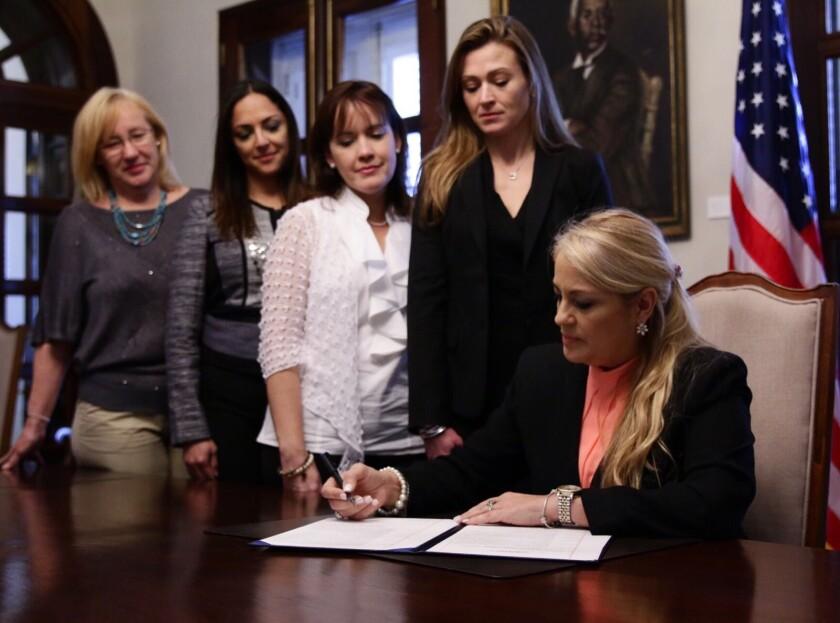 Puerto Rico Governor Wanda Vazquez signing a document