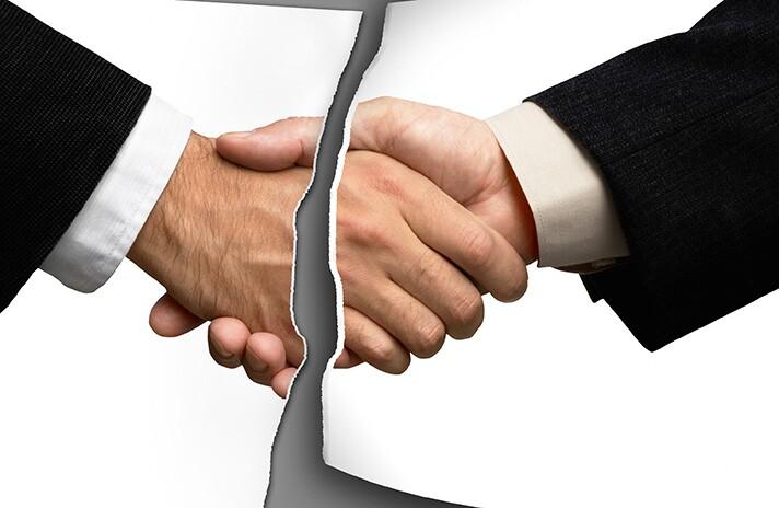 Photo of handshake deal torn in half.