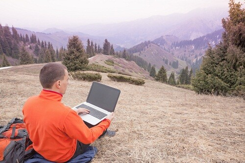 man dressed in red sweater uses laptop remotely with 3g or 4g network wireless at mountain, square orientation