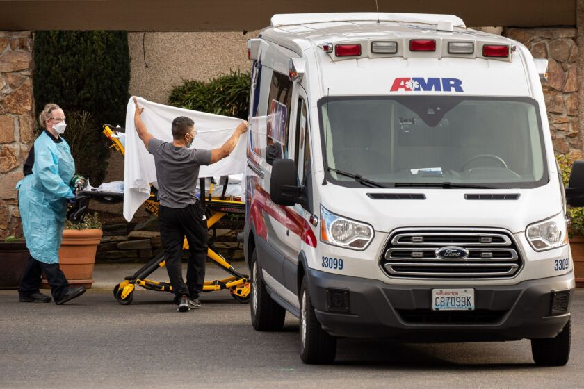Health care workers transport a patient on a stretcher into an ambulance at Life Care Center of Kirkland, Washington.