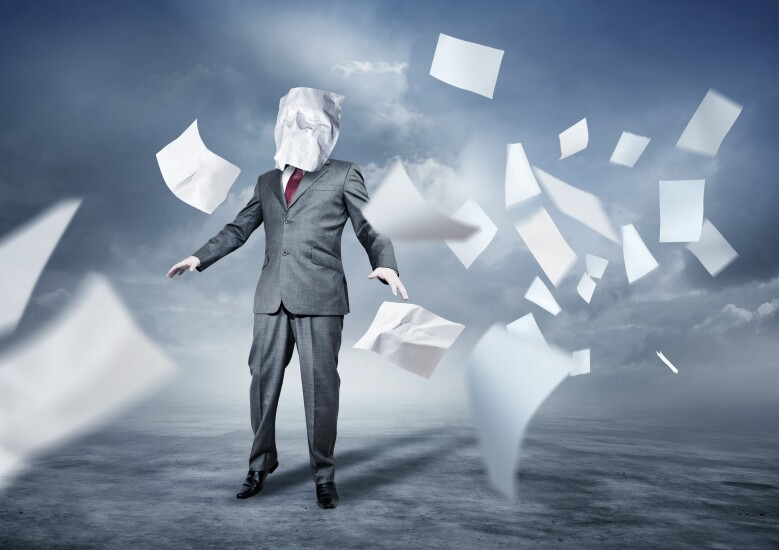 Businessman overwhelmed by swirling paperwork.