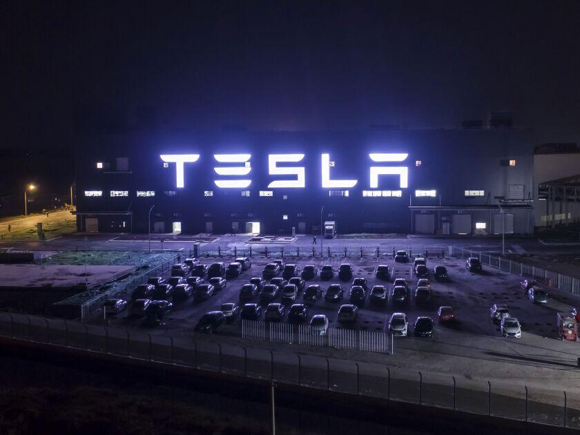 Tesla sign illuminated at night.
