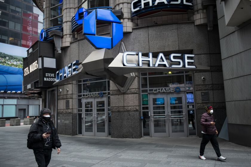 Pedestrians wearing protective masks walk past a JPMorgan Chase bank branch in New York on April 10, 2020.