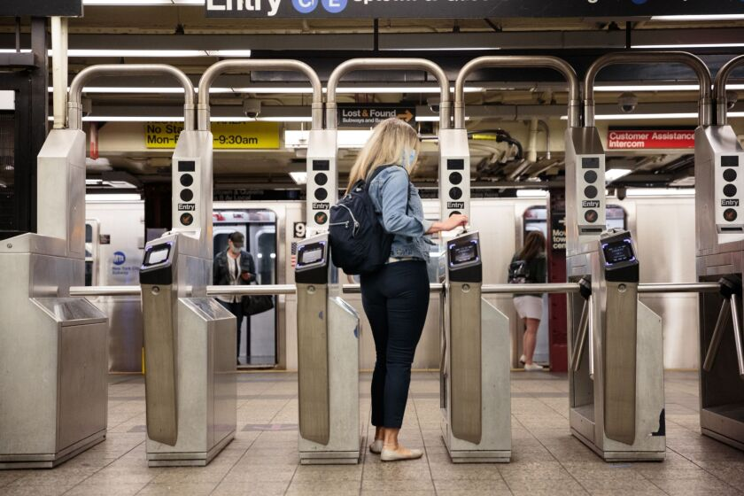 A commuter wearing a protective mask swipes a metro card through a turnstile slot at a subway station in New York