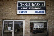 Signage advertising income tax service is pictured in front of Tax Pros USA in La Grange, Kentucky, U.S., on Wednesday, April 9, 2014. The deadline for filing federal income tax returns to the Internal Revenue Service is Tuesday, April 15. Photographer: Luke Sharrett/Bloomberg