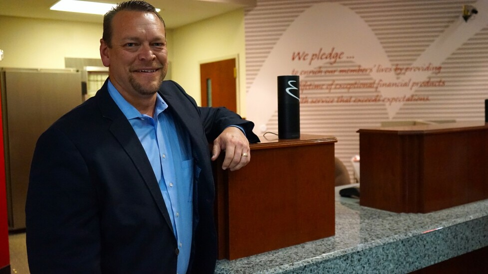 John Merritt, chief information officer at Enrichment Federal Credit Union, poses with one of the Echo Dot devices the CU gave employees to help roll out voice banking via Amazon's Alexa service.