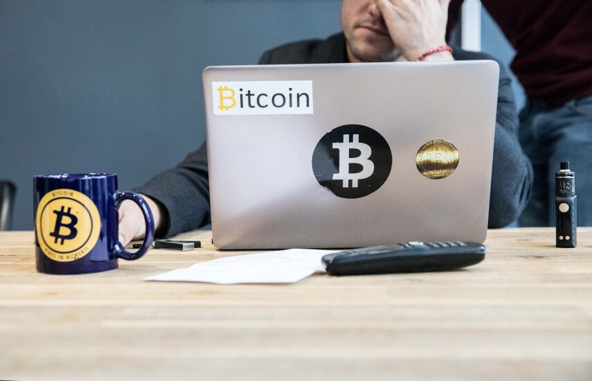 An employee uses a laptop computer branded with bitcoin logos inside the offices of La Maison du Bitcoin bank in Paris.