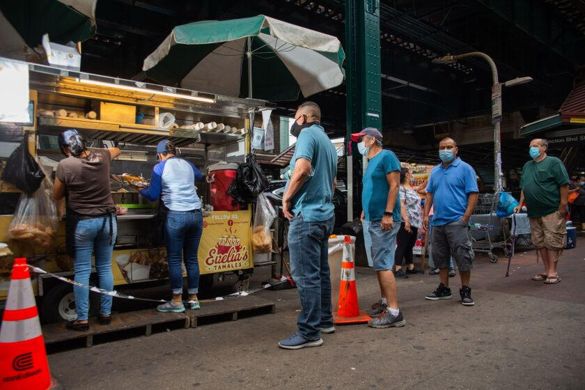 Customers stand in line outside Evelia's Tamales food cart.
