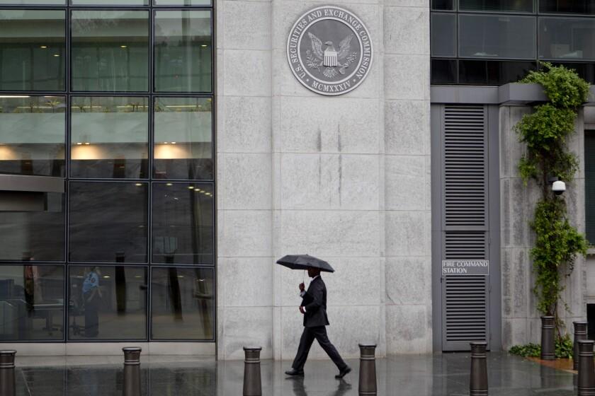 SEC building man umbrella - Bloomberg News