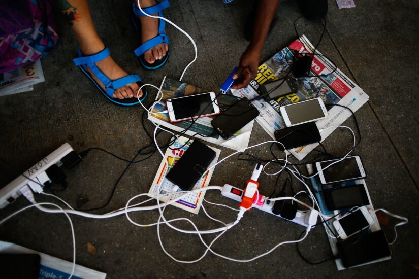 People charge their mobile devices outside a Wal-Mart Stores Inc. location in San Juan, Puerto Rico, on Thursday, Sept. 28, 2017.