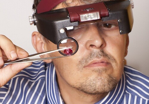 Male jeweler looking through a magnifier to check for flaws in a ruby.  Focus on ruby