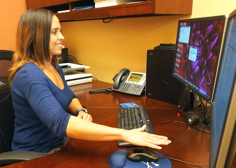 Hughes Federal Credit Union Manager Mary Burruel using a Verifast palm-biometric mouse to authenticate at her desk.