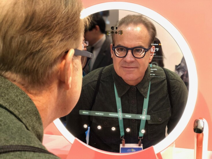 """Todder Moning, product innovation director at U.S. Bank, examines a """"smart mirror"""" at CES 2020."""
