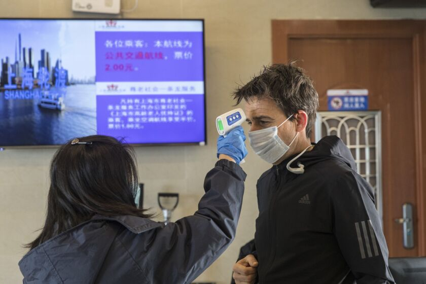 A transit worker takes the temperature of a passenger during a screening at a passenger ferry terminal in Shanghai, China.