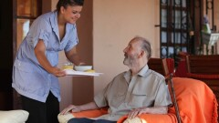 nurse or helper in residential home giving food to old senior man