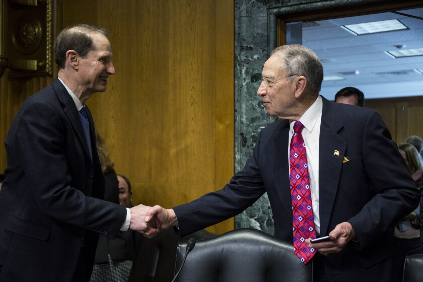 Senate Finance Committee ranking member Ron Wyden, D-Ore. (left), shakes hands with committee chairman Chuck Grassley, R-Iowa.