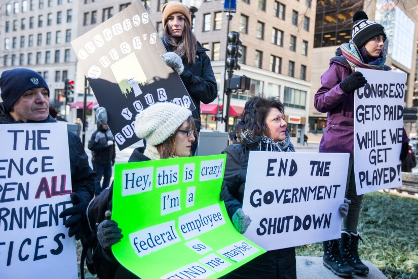 Demonstrators hold signs in Boston during a protest against the government shutdown.