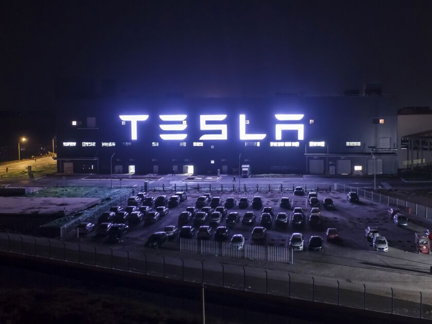 Tesla sign illuminated at night.