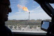 A gas flare is seen through the window as a Royal Dutch Shell Plc representative drives near Mentone, Texas.
