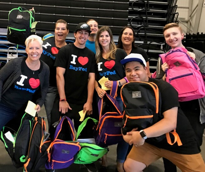 """In Capitola, Calif., Bay Federal Credit Union's CEO Carrie Birkhofer (top row, far right) poses with employees at a United Way """"Stuff the Bus"""" back to school backpack drive for homeless youth."""