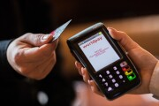 A customer holds a contactless debit card issued by HSBC near a Worldpay payment terminal.