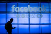 An attendee looks at a mobile phone while walking under a Facebook logo in the demonstration room during the F8 Developers Conference in San Jose, California, on April 30, 2019.