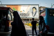Pedestrians pass in front of a political mural in Tehran depicting Ruhollah Khomeini, founder of the Islamic republic of Iran.