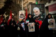 Mourners carry images of Iranian General Qassem Soleimani during the funeral ceremony in Tehran, Iran, on Monday, Jan. 6, 2020.