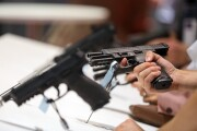 An attendee holds a pistol during the Defense and Security Equipment International exhibition at Excel in London.