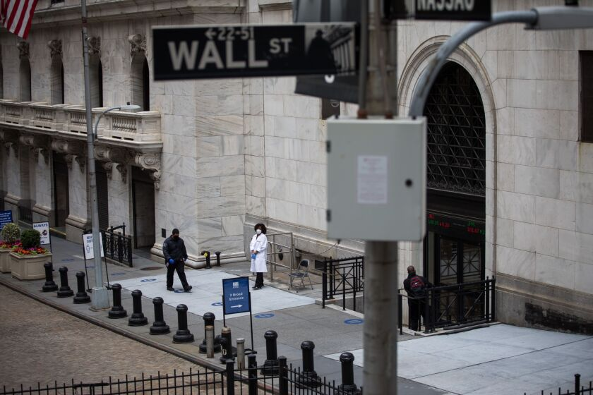 A healthcare worker stands in front of an entrance to the New York Stock Exchange (NYSE) in New York, U.S., on Wednesday, June 3, 2020. After more than two months in lockdown, this heart of global capitalism, the biggest city in the world's biggest economy, faces a moment that couldn't feel more fraught or have higher stakes. Photographer: Michael Nagle/Bloomberg