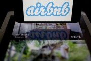 The Airbnb logo and app displayed on an Apple iPhone and iPad