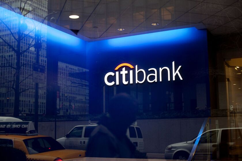 A pedestrian is reflected in a Citigroup bank branch.
