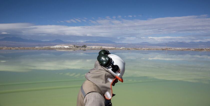 A visitor walks past a brine lake at a lithium mine on the Atacama salt flat in the Atacama Desert, Chile.