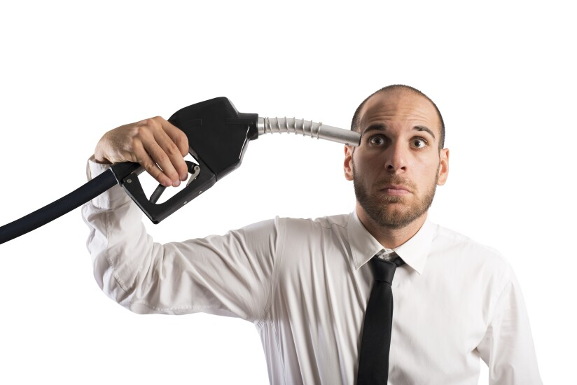 Man holding gasoline pump to his head