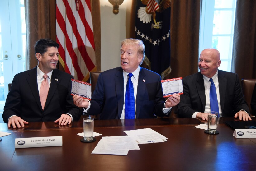 "U.S. President Donald Trump, center, speaks while holding up ""Simple, Fair, 'Postcard' Tax Filing"" cards as U.S. House Speaker Paul Ryan, a Republican from Wisconsin, left, and Representative Kevin Brady, a Republican from Texas and chairman of the House Ways and Means Committee, react during a meeting in the Cabinet Room of the White House in Washington, D.C., U.S., on Thursday, Nov. 2, 2017. The House tax bill released Thursday preserves the carried interest tax break despite Trump and GOP leaders' promise to do away with loopholes for the wealthy."
