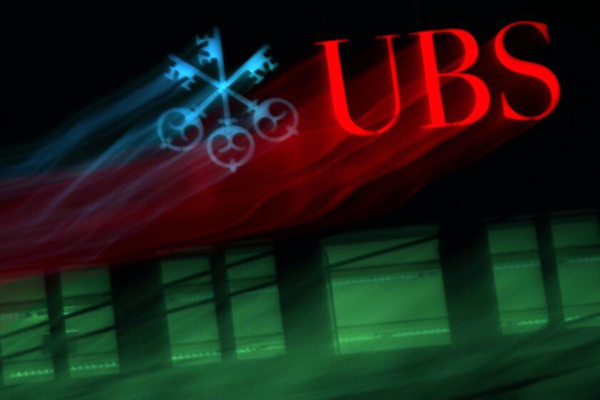 An illuminated company logo is displayed at a UBS Group AG bank branch in Zurich, Switzerland, on Monday, Oct. 14, 2019. The spying scandal roiling Credit Suisse Group AG has also created a big headache at UBS a stone's throw away in Zurich: What to do about its star hire Iqbal Khan. Photographer: Stefan Wermuth/Bloomberg