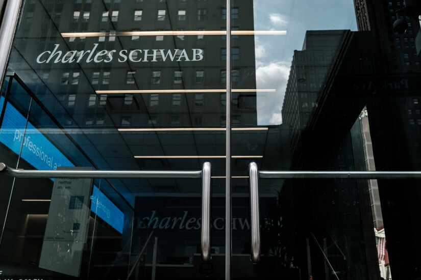 Charles Schwab Corp. signage is displayed on the door of an office building in New York, U.S., on Thursday, April 12, 2018. Charles Schwab Corp. reported earnings per share for the first quarter that beat the average analyst estimate, with 443,000 new accounts, the highest quarterly level in 18 years, chief executive officer Walt Bettinger said in a statement. Photographer: Christopher Lee/Bloomberg