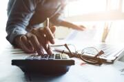 Closeup of an accountant's hand on a calculator.