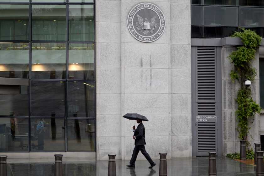 SEC building man umbrella - Bloomberg News