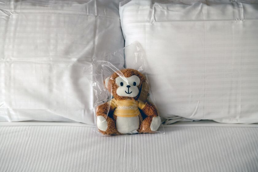 A Covid-proofed stuffed monkey sits on an empty bed in a New York hotel. Millennials are opting for stay-cations, saving money that, when added to their stimulus checks, can fuel financial wealth.