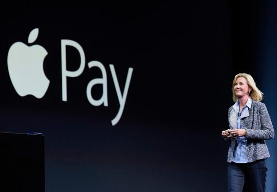 Apple VP Jennifer Bailey walks past Apple Pay logo for speech.