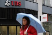 A pedestrian shelters under an umbrella while passing a UBS Group AG bank branch in Zurich, Switzerland, on Monday, Jan. 22, 2018.