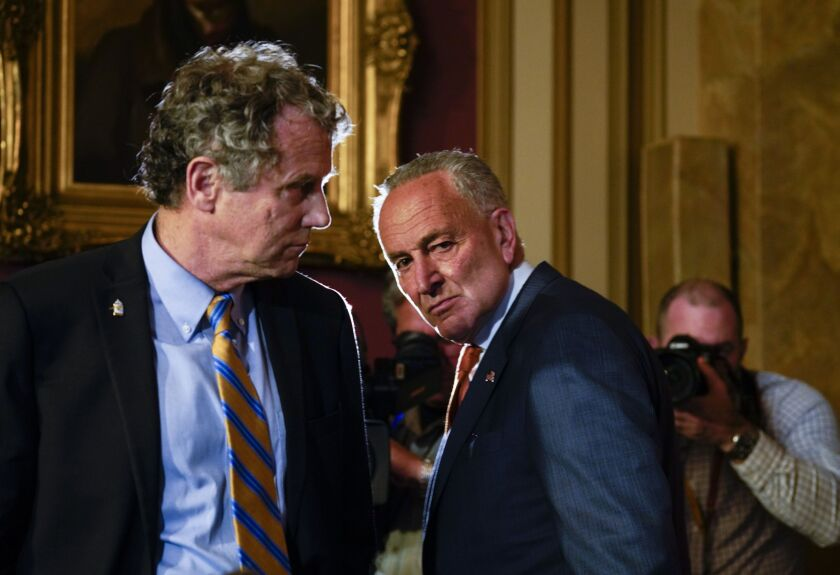 Democrats like Sen. Sherrod Brown of Ohio, left, supported measures such as a temporary ban on overdraft fees. But many consumer protection proposals did not make it in to the final stimulus package negotiated by Senate Minority Leader Chuck Schumer, D-N.Y.