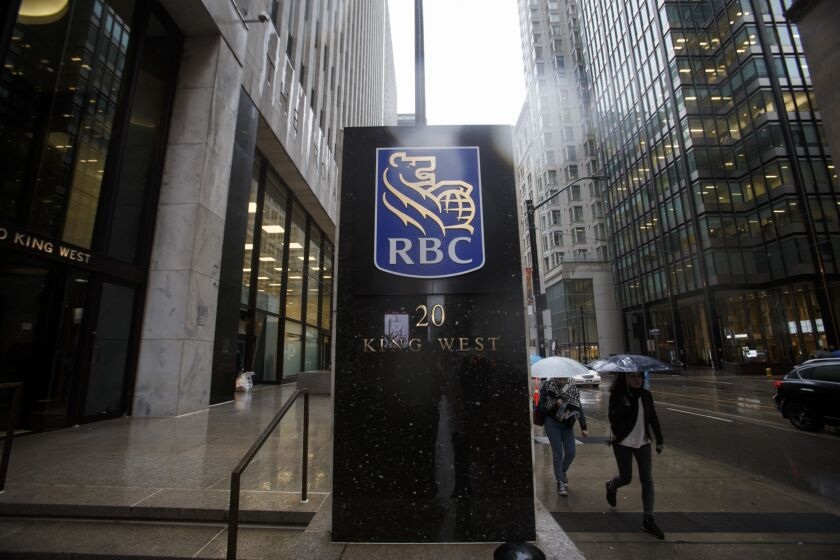 Pedestrians carry umbrellas while walking past Royal Bank of Canada (RBC) signage displayed at the Royal Bank Building during the company's annual general meeting in Toronto, Ontario, Canada, on April 6, 2017. RBC Chief Executive OfficerDavid urged lawmakers to coordinate interventions and act quickly to cool housing markets, particularly in Toronto and Vancouver. Photographer: Cole Burston/Bloomberg