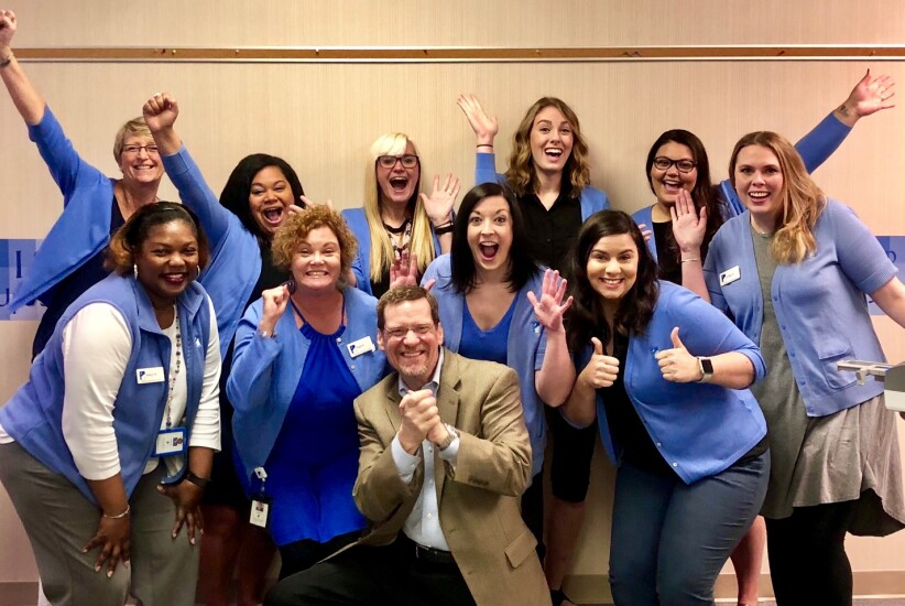 CEO Scott Woods celebrates with South Carolina Federal Credit Union's Service and Support Managers after learning that the credit union's performance-management model would shift to one of continuous feedback, rather than formal, semi-annual performance reviews